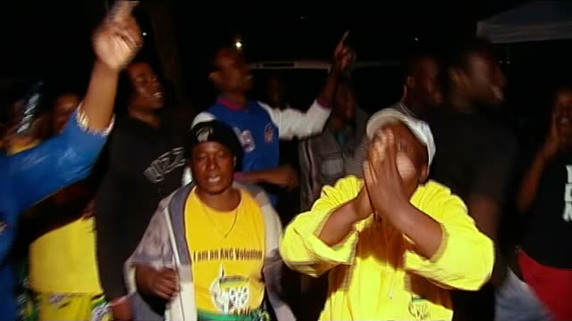 nelson mandela's condition improves; south africa: pretoria: night women and men singing, dancing and blowing whistles on street man holding lit... - ハウテング州点の映像素材/bロール