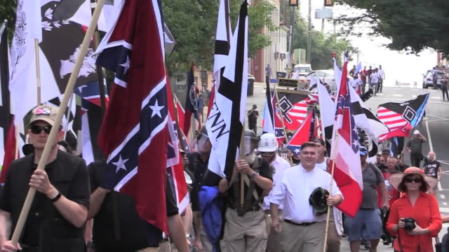 vídeos de stock e filmes b-roll de neo nazi rally hate groups wear trump hats in streets of charlottesville virginia david duke briefly - comício político
