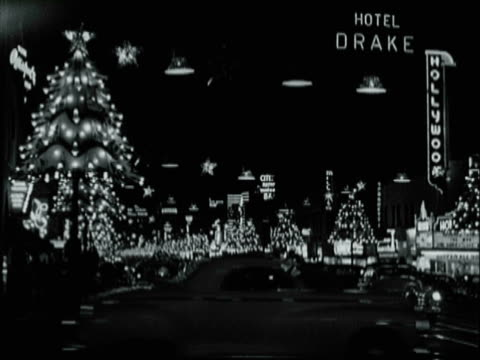 montage neon and christmas lights illuminating hollywood boulevard / los angeles, california, united states - anno 1957 video stock e b–roll