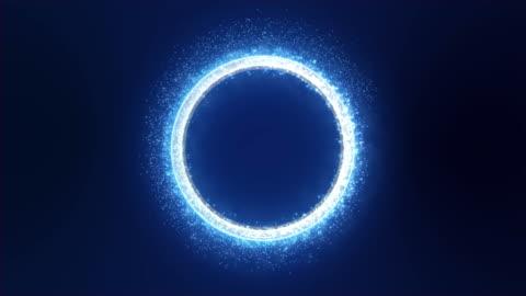 vídeos de stock e filmes b-roll de neon blue light with sparkle and smoke trail creates a round metallic three-dimensional ring. dark blue background. - circle