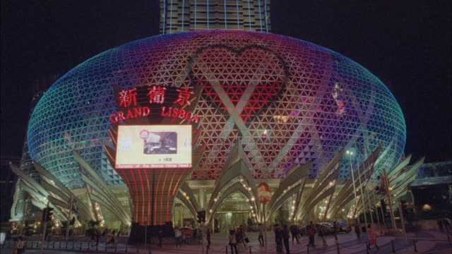 neon images of playing cards appear on a dome-shaped building. - macao stock videos & royalty-free footage