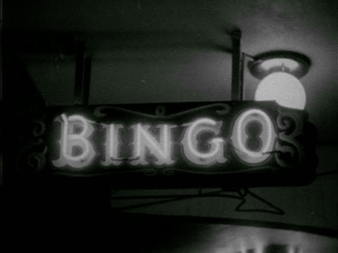 Neon letters 'Bingo' on sign hanging from ceiling w/ flashing arrow below Direction directing pointing gaming games