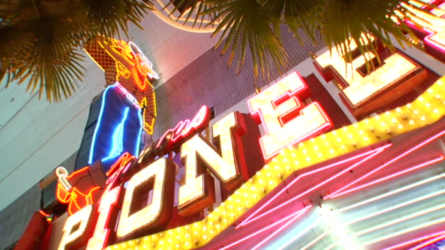 Neon lighted cowboy VEGAS VIC standing above lighted Pioneer sign Gambling wagering night life Lifestyle glitz glitter gulch Iconic Icon refurbished...