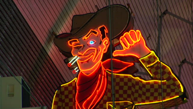 neon lighted cowboy vegas vic w/ cigarette in mouth blue eye winking glitter gulch icon iconic originally part of pioneer casino sign refurbished arm... - casino icon stock videos & royalty-free footage