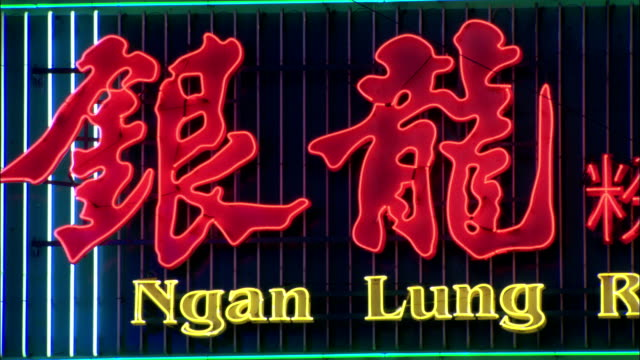Neon lights flash across red Chinese characters. Available in HD.