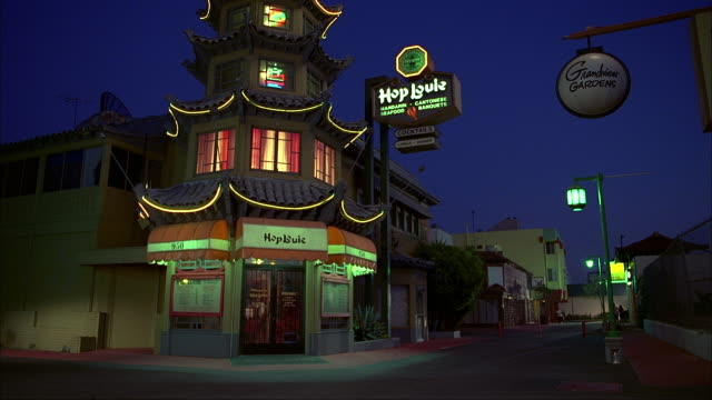 neon lights flashing on a sign outside the hop louie restaurant. - western script stock videos & royalty-free footage