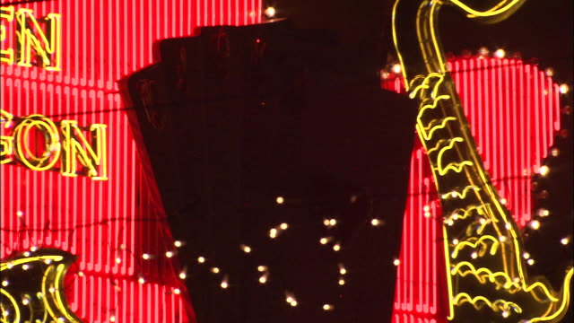 neon lights form shuffling playing cards on a neon sign at night. - macao stock videos & royalty-free footage