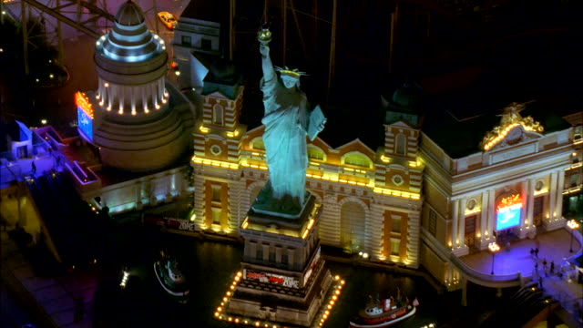 vídeos de stock, filmes e b-roll de neon lights illuminate a replica of the statue of liberty outside the new york-new york hotel and casino. available in hd. - réplica da estátua da liberdade réplica