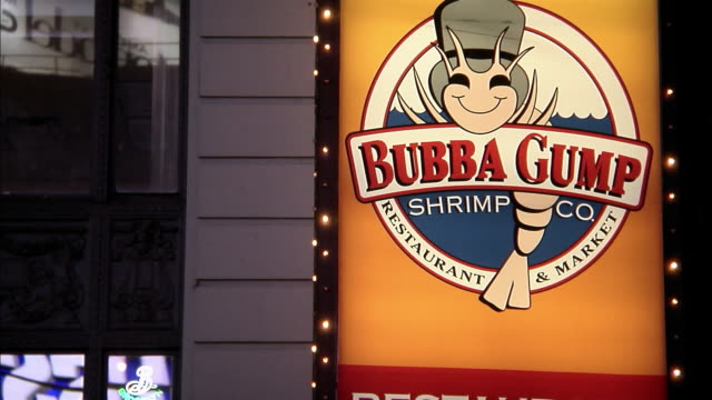 neon lights illuminate a sign for bubba gump shrimp co. restaurant & market. - theatre district stock videos & royalty-free footage