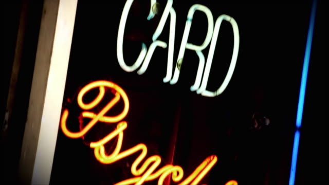 Neon lights illuminate a sign for tarot card readings and a psychic.