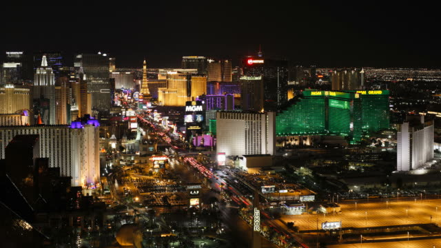 neon lights illuminate las vegas boulevard as traffic travels past casinos and hotels. - the strip las vegas stock videos & royalty-free footage