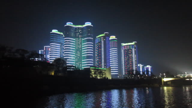 neon lights illuminate modern buildings in the center of pyongyang. - pyongyang stock videos and b-roll footage