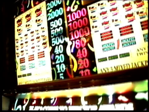neon lights illuminate slot machines at bally's hotel and casino in las vegas, nevada. - bally's las vegas stock videos & royalty-free footage