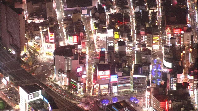 Neon lights illuminate stores as traffic and pedestrians move on busy streets near Shinjuku Station