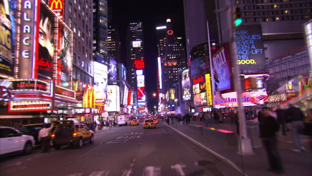 Neon lights illuminate streets and sidewalks in Times Square at night.