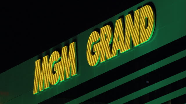 neon lights illuminate the mgm grand hotel and casino sign. - mgm grand las vegas stock videos & royalty-free footage