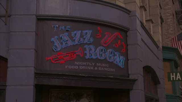 neon lights illuminating the jazz room bar sign. - poster stock-videos und b-roll-filmmaterial