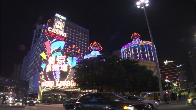Neon lights on a dome shaped casino flash and illuminate the night sky.