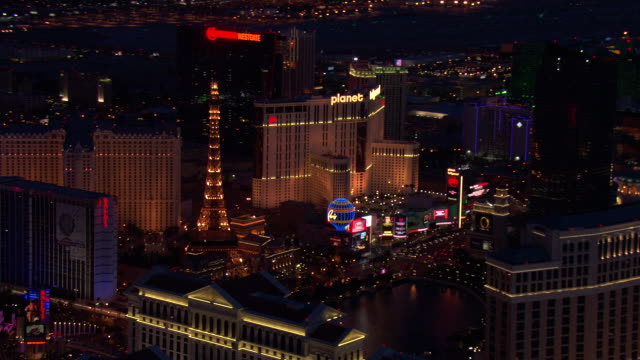 neon lights sparkle on the paris hotel and casino and planet hollywood in las vegas. - clark county nevada stock videos and b-roll footage