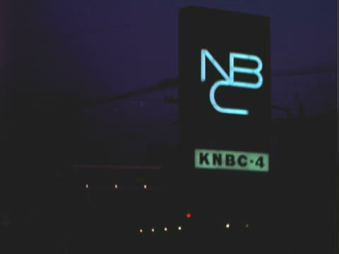 vidéos et rushes de montage neon lit network broadcasting sign at night while traffic passes by / los angeles, california, united states - nbcuniversal