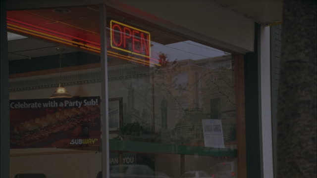 stockvideo's en b-roll-footage met a neon open sign hangs in the window of a sandwich shop on a city street. - dineren