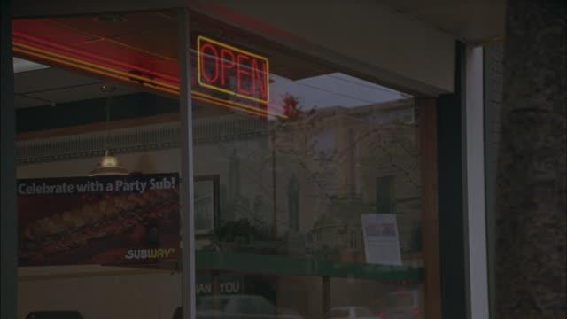 a neon open sign hangs in the window of a sandwich shop on a city street. - dinera bildbanksvideor och videomaterial från bakom kulisserna