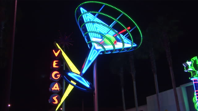 a neon sign depicts a martini glass. - martini glass stock videos and b-roll footage