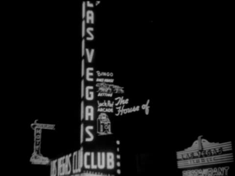 Neon sign 'Las Vegas Club' MS Female playing slot machine MS Folded bill amp change dropping down slot Gambling gaming bet betting luck high risk fun...