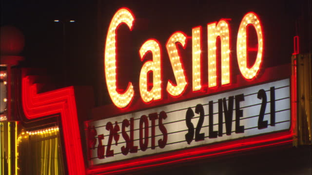 a neon sign on a casino flashes on and off. - entrance sign stock videos & royalty-free footage