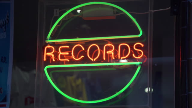 "neon sign saying ""records"" in the window of a music record store - neon stock videos & royalty-free footage"
