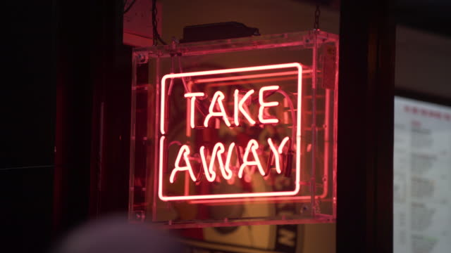 A neon sign saying 'Take Away' glows in a restaurant window