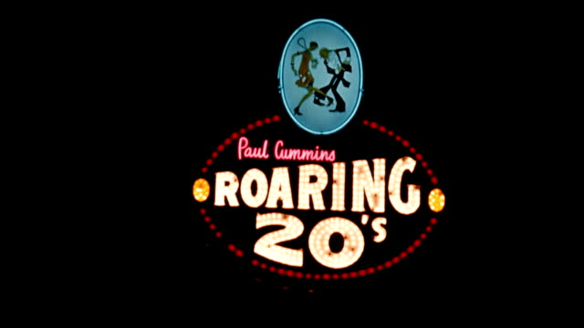 vídeos de stock e filmes b-roll de / neon sign that reads 'paul cummins roaring 20s' / well dressed patrons enter roaring 20s restaurant / woman swinging from the ceiling smiling... - bar clandestino