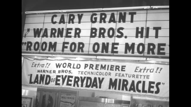 VS neon sign 'Warner' with pan down to theater marquee 'Cary Grant Warner Bros hit Room for one More World Premiere Warner Bros Technicolor Land of...