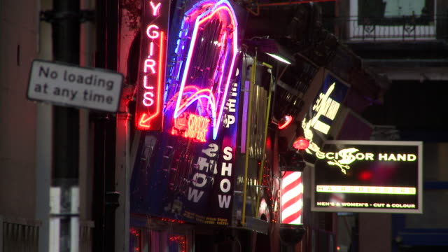 Neon signs advertise peep shows in London's Soho district.