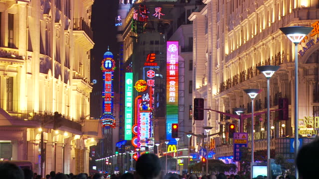 neon signs and buildings along nanjing road in shanghai china - nanjing stock-videos und b-roll-filmmaterial