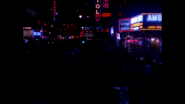 WS Neon signs and theater marquees in Times Square at night / New York City, New York State, United States
