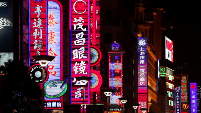 neon signs flash and shine above shops along nanjing road in shanghai. - nanjing road stock videos & royalty-free footage