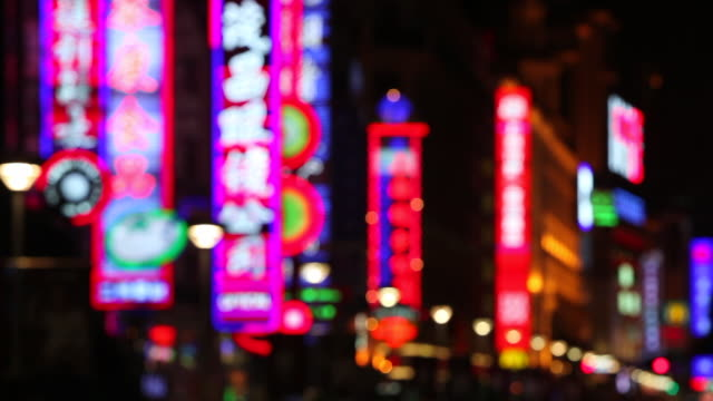 neon signs flash and sparkle above shops along nanjing road in shanghai. - nanjing road stock videos & royalty-free footage