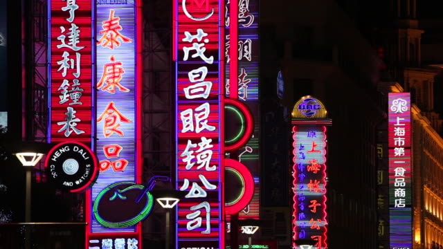 Neon signs flash and sparkle above shops along Nanjing Road in Shanghai.
