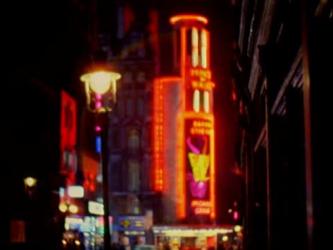 neon signs hanging from theatre buildings in soho commercial district / pedestrians walk sidewalks / entrance to drury lane theatre at night. soho... - 1966 stock videos & royalty-free footage