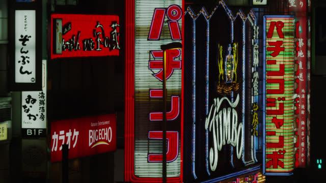 cu neon signs near shinjuku west railway exit (odakyu eki mae) / tokyo, tokyo-to, japan - lingua giapponese video stock e b–roll
