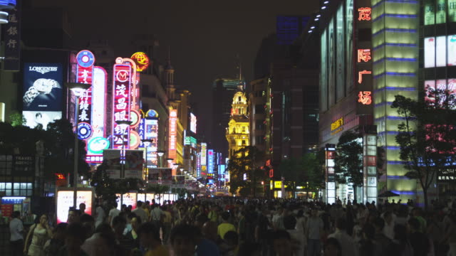 neon signs shed light on a massive crowd walking down a street. - mcdonald's stock videos and b-roll footage