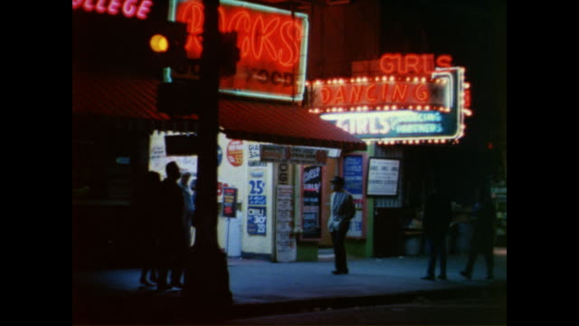 / neon store and burlesque club signs illuminated at night / men staring through window of sports store / theater marquee for 'bonnie clyde' 'up the... - 1968 stock videos & royalty-free footage