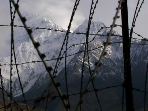cu, nepal, jomsom, barbed wire with snow capped annapurna mountains in background - annapurna range stock videos and b-roll footage