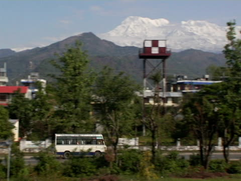 MS, TS, Nepal, Pokhara, Bus driving through city, Annapurna Mountains in background