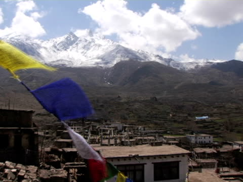 cu, nepal, tibetan buddhist prayer flags with village and snow capped annapurna mountains in background - annapurna range stock videos and b-roll footage