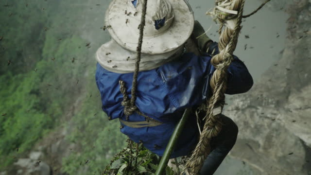Nepalese honey farmer waves from side of mountain in slow motion
