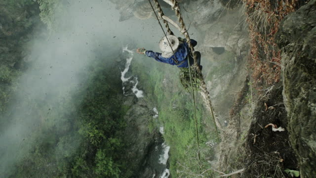 Nepalese honey farmer waves from side of mountain in slow motion, wide shot