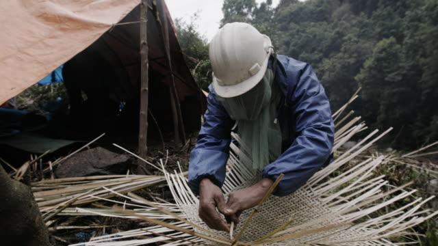 Nepalese man weaves basket