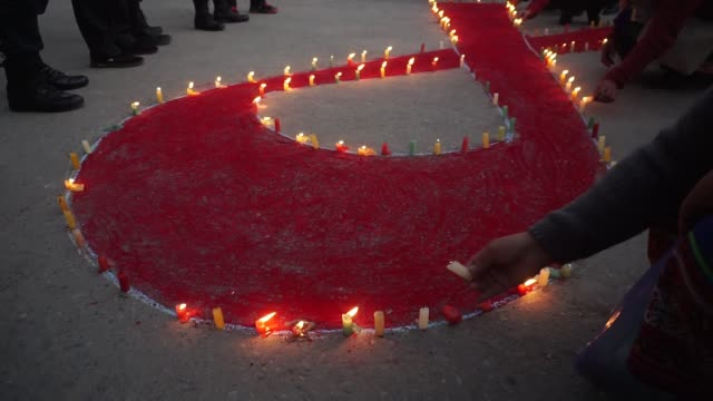 nepalese women and children light candles forming the 'red ribbon' symbol as they pray for those who have lost their lives due to hiv/aids, on the... - aids awareness ribbon stock videos & royalty-free footage